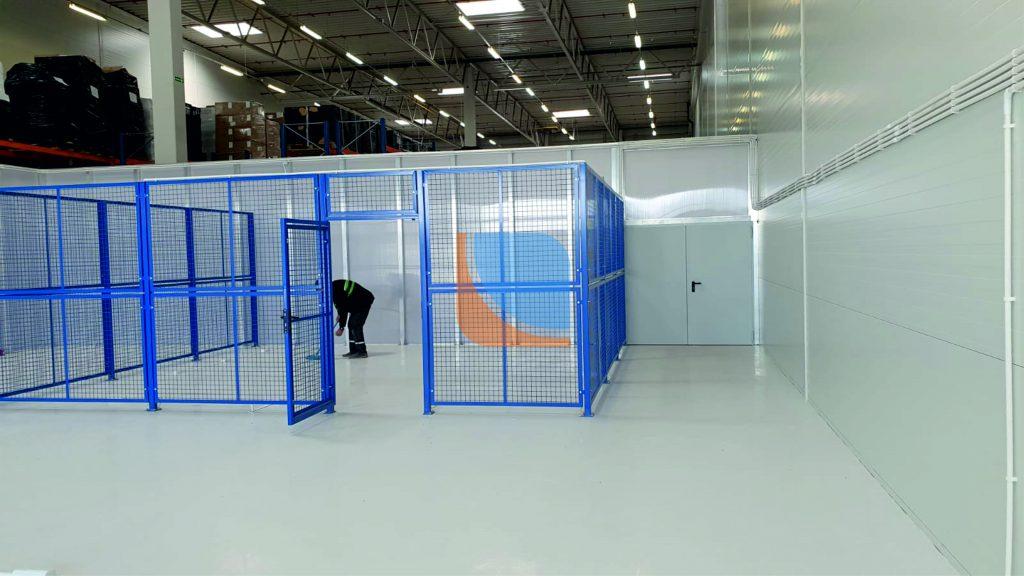 ścianka działowa na hali produkcyjnej z niebieskim ogrodzeniem